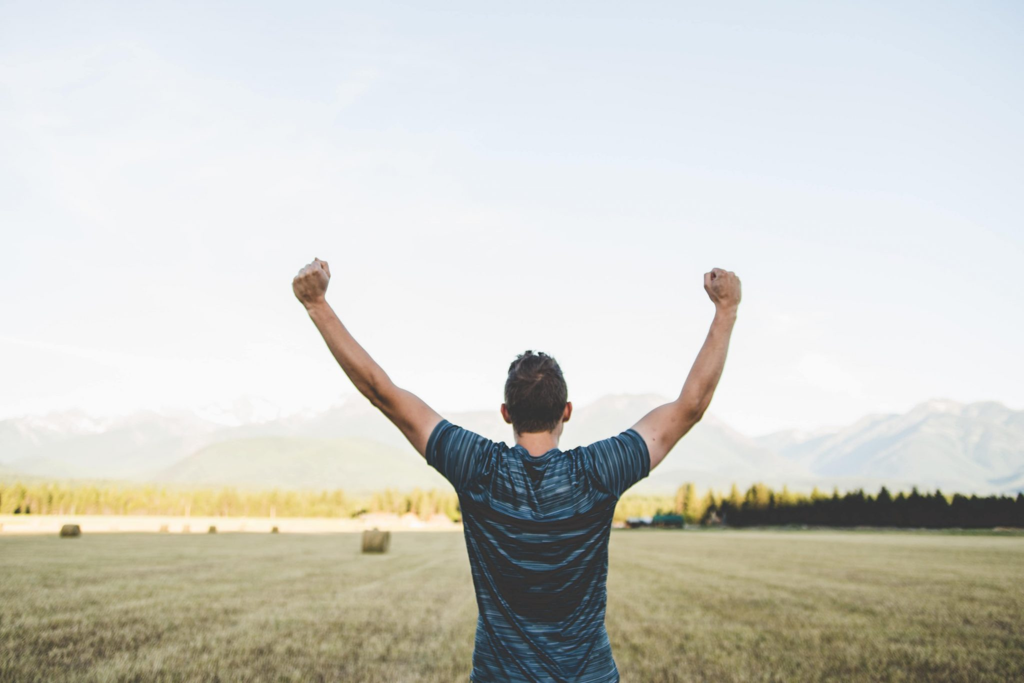 Man raising hands in victroy from experiencing hope and healing from Christian Counseling in Jenison MI offered by Great Lakes Wellness Counseling